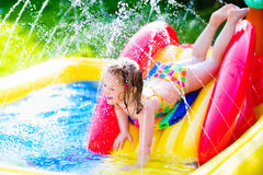 Little girl playing in inflatable garden swimming pool Stock Images