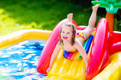 Little girl playing in inflatable garden swimming pool. Children playing in inflatable baby pool. Kids swim and splash in colorful garden play center. Happy Stock Photography