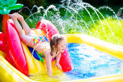 Little girl playing in inflatable garden swimming pool. Children playing in inflatable baby pool. Kids swim and splash in colorful garden play center. Happy Royalty Free Stock Photography