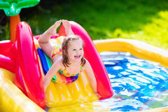 Little girl playing in inflatable garden swimming pool Royalty Free Stock Photography