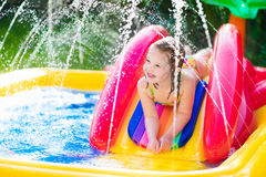 Little girl playing in inflatable garden swimming pool Royalty Free Stock Photo