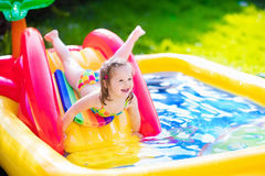 Little girl playing in inflatable garden swimming pool Royalty Free Stock Photos