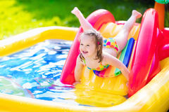 Little girl playing in inflatable garden swimming pool Stock Image