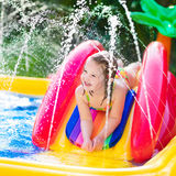Little girl playing in inflatable garden swimming pool Stock Photo