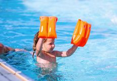 Little girl playing with inflatable ring in outdoor swimming pool on hot summer day. Kids learn to swim. Child water toys. Family stock photo