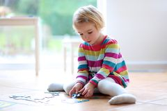 Little girl playing with jigsaw puzzle stock photography