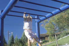 A little girl playing on the jungle gym, NM Royalty Free Stock Photos