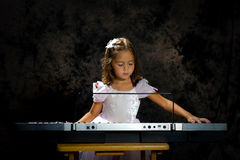 Little Girl playing a keyboard straoght on royalty free stock image