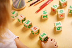 Little girl playing with kid math cubes Stock Images