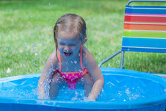 Little Girl Playing in a Kiddie Pool. Little Girl Wearing Pink Bathing Suit Playing in a Kiddie Pool Royalty Free Stock Image