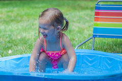 Little Girl Playing in a Kiddie Pool. Little Girl Wearing Pink Bathing Suit Playing in a Kiddie Pool Royalty Free Stock Images