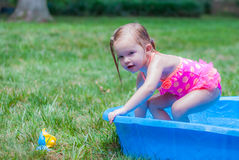 Little Girl Playing in a Kiddie Pool. Little Girl Wearing Pink Bathing Suit Playing in a Kiddie Pool Stock Image