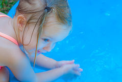 Little Girl Playing in a Kiddie Pool. Little Girl Wearing Pink Bathing Suit Playing in a Kiddie Pool Royalty Free Stock Photos
