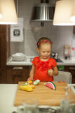 Little girl playing in the kitchen with fruits and Stock Images