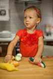 Little girl playing in the kitchen with fruits and Stock Photo
