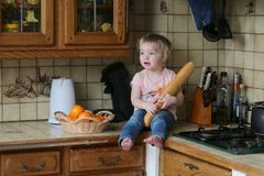 Little girl playing in the kitchen Stock Photos