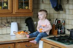 Little girl playing in the kitchen Stock Images
