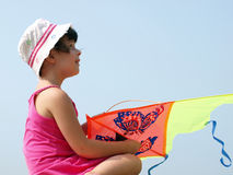 Little girl playing with a kite. On a background of blue sky stock image