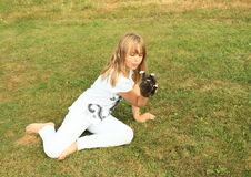 Little girl playing with a kitty. Smiling girl - little kid in white clothes holding small black kitty in hand Stock Photo