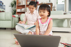 Little girl playing laptop royalty free stock photography