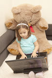 Little girl playing on laptop. In a teddy lap Stock Photography