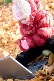 Little girl playing with laptop in autumn park Royalty Free Stock Photography