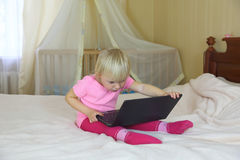 Little girl playing with a laptop on the big bed Royalty Free Stock Photo