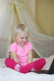 Little girl playing with a laptop on the big bed Royalty Free Stock Image