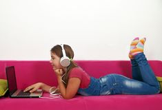 Little girl playing laptop and listening music Stock Images