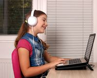 Little girl playing laptop and listening music on headphon Stock Photography
