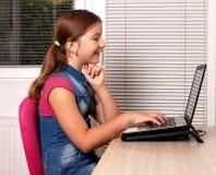 Little girl playing laptop Stock Image