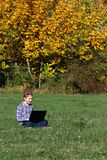 Little girl playing laptop in the park autumn season Royalty Free Stock Images