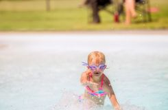 Little girl playing and laughing in a swimming pool stock images