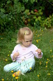 Little girl playing on the lawn Stock Photos