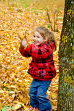 Little girl playing with leaves Royalty Free Stock Photo