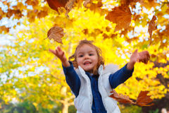Little girl playing with leaves Royalty Free Stock Images