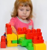 A little girl playing with Lego blocks Stock Photo