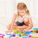 Little girl playing Lego on the floor Stock Photo