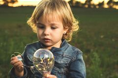 Little girl playing with a light bulb. Children playing royalty free stock photo