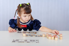 Little girl playing with lotto sitting at table Stock Photo