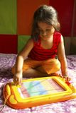 Little girl playing with magnetic drawing board, Pune, Maharashtra, India.  royalty free stock photography