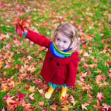Little girl playing with maple leaf in autumn. Little girl with yellow leaf. Child playing with autumn golden leaves. Kids play outdoors in the park. Children Stock Images