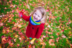 Little girl playing with maple leaf in autumn. Little girl with yellow leaf. Child playing with autumn golden leaves. Kids play outdoors in the park. Children Royalty Free Stock Photo