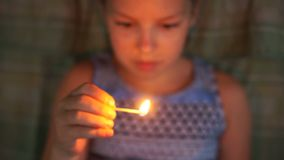 Little girl playing with matches, at the risk of setting the fire. Fire safety.  stock video