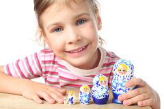 Little girl playing with matryoshka and smiling Stock Photos