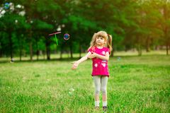 Little girl playing on the meadow on sun with windmill in her hands. Child holding wind toy stock photos