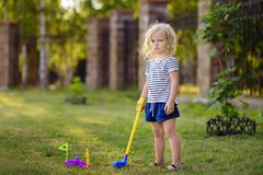 Little girl playing mini golf in spring park. Frustrated child, failure, missed. Little girl playing mini golf in spring park. Child having fun with active royalty free stock photos