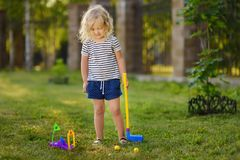 Little girl playing mini golf in spring park. Frustrated child, failure, missed stock photos