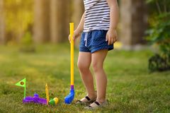 Little girl playing mini golf in spring park. Child having fun with active leisure on vacations royalty free stock images