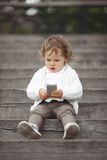 Little girl playing with mobile phone Stock Images